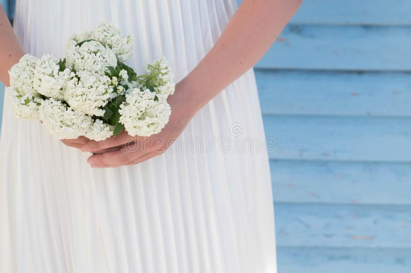 Slender woman in white satin pleated dress holding a small bouquet of white flowers in hands on a blue lath background with. Copyspace. Use for card design, for stock photos