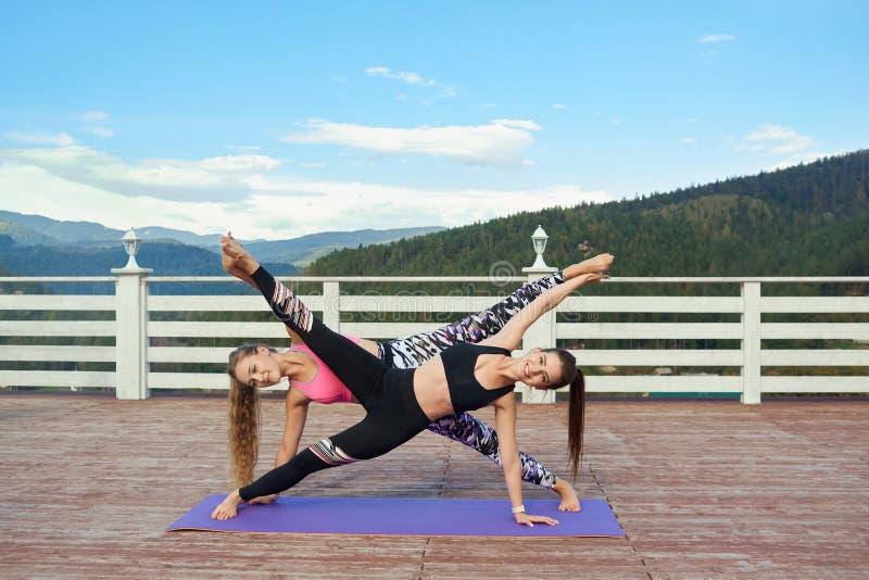 Slender women stretching together on yoga mats. Beautiful, slender girls practicing sretching together. Flexible women doing yoga on yoga mat outdoors on fresh stock image
