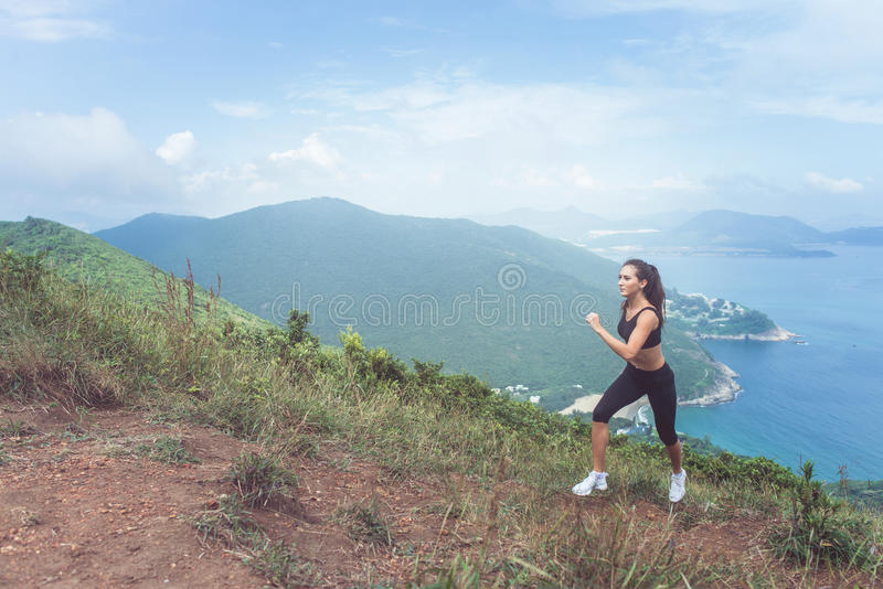Slender young female athlete doing cardio exercise going up the mountain with sea in background. stock photo