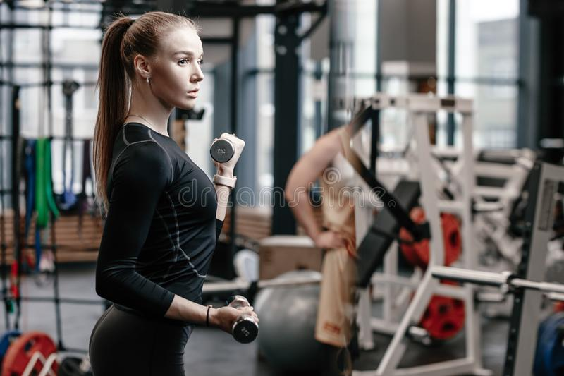 Slender young girl dressed in a black sportswear is doing exercises with dumbbells in the modern gym with lots of sport stock photo