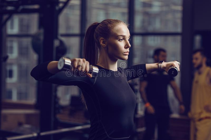 Slender young girl dressed in a black sportswear is doing exercises with dumbbells in the modern gym with lots of sport stock photos