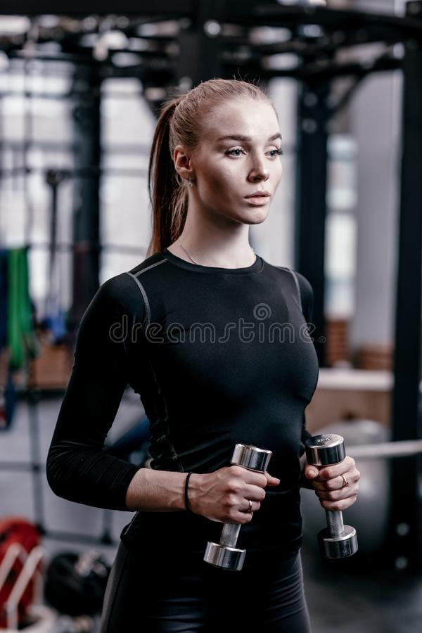Slender young girl dressed in a black sportswear is doing exercises with dumbbells in the modern gym with lots of sport stock image