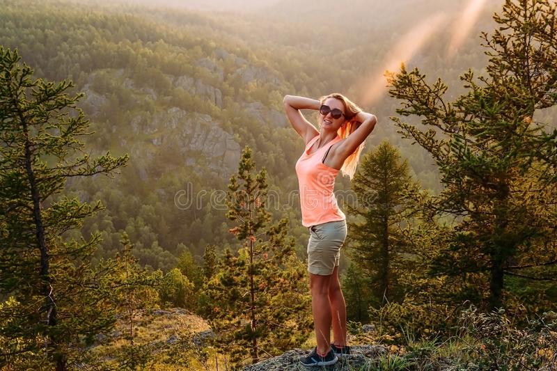 A slender young smiling long-haired woman in a t-shirt and shorts stands on the mountain in the summer. Woman at dawn in the stock photo