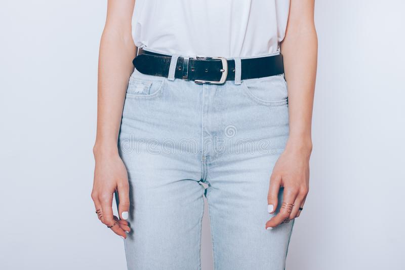 Slender young woman wearing blue high waist jeans stock photos