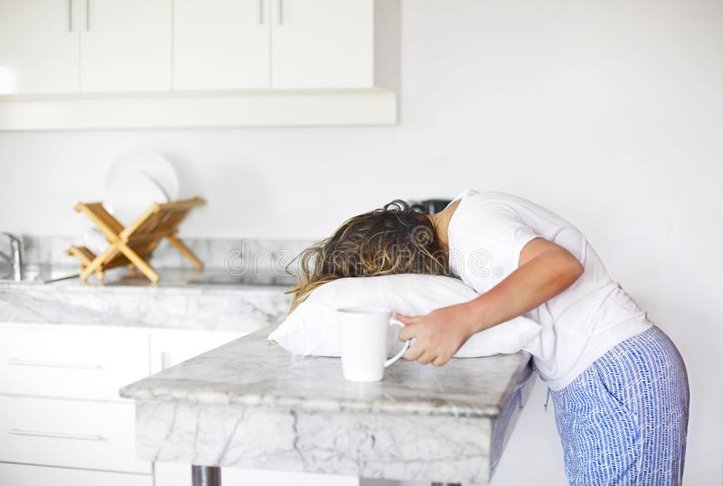 Sleppy woman with cup of coffee and pillow on the kitchen in morning. Hard morning wake up concept royalty free stock image
