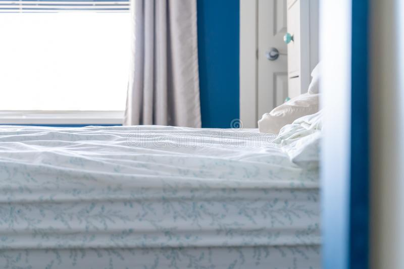 A slept-in bed with a messy sheet, no blankets, in a blue and white bedroom home design. Low angle view of a slept-in bed with a messy sheet, no blankets, in a stock image