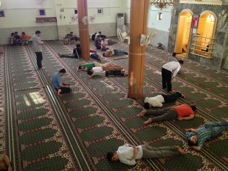People resting inside a muslim mosque stock photos