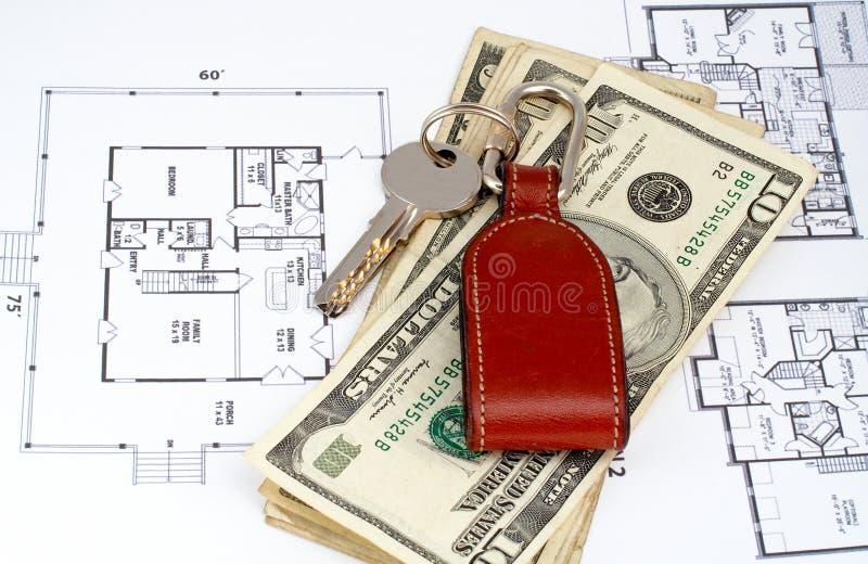 Sleutel en geld op huisplan stock afbeeldingen