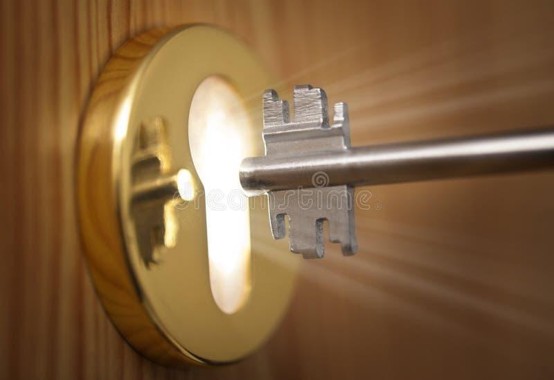 Sleutel en sleutelgat met licht royalty-vrije stock fotografie