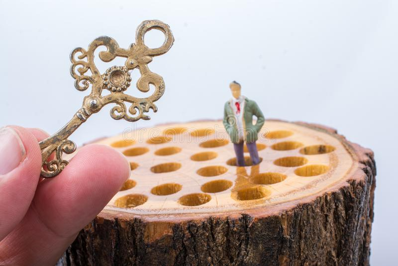 Sleutel en van weinig mensenbeeldje plaatsen op houten logboek royalty-vrije stock afbeeldingen