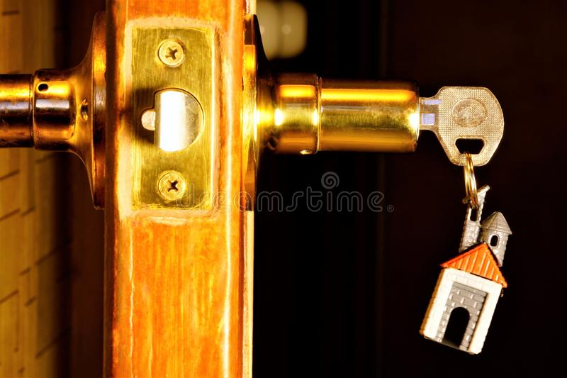 Sleutel met een keychain in de vorm van een huis in het deurslot Het belangrijkste hulpmiddel aan open sloten voor aanwijzingen,  stock afbeelding
