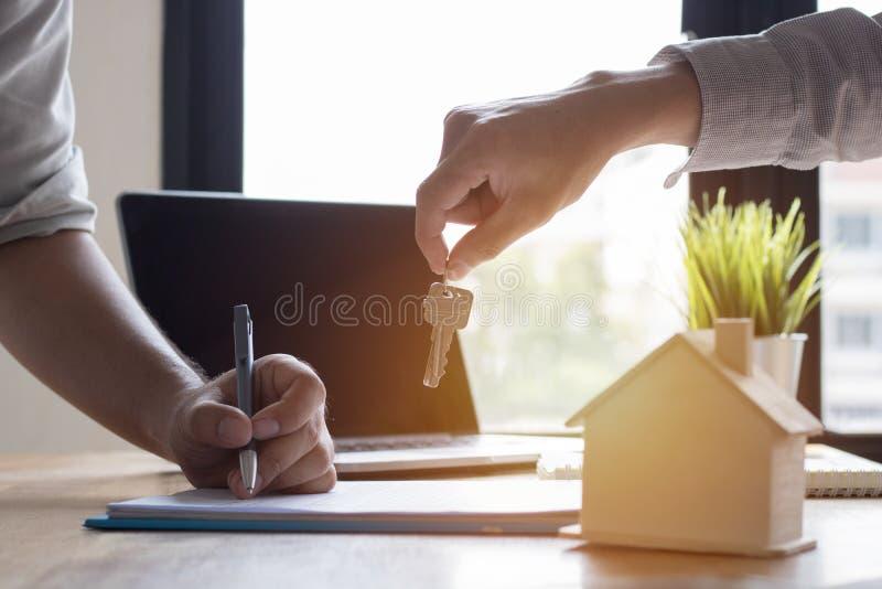 Sleutel van huis op hand van bank employeer om huis na appro te verkopen stock afbeeldingen