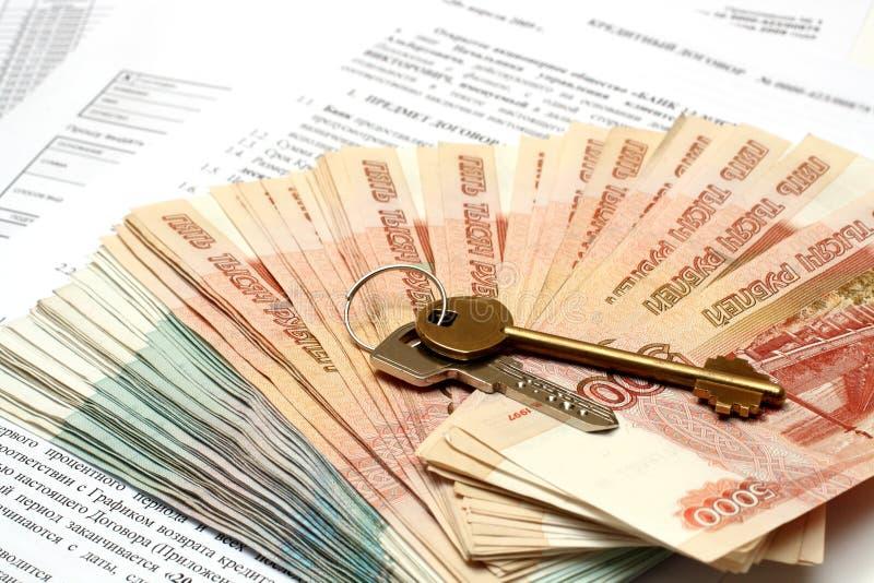 Sleutels en geld op kredietcontract royalty-vrije stock foto