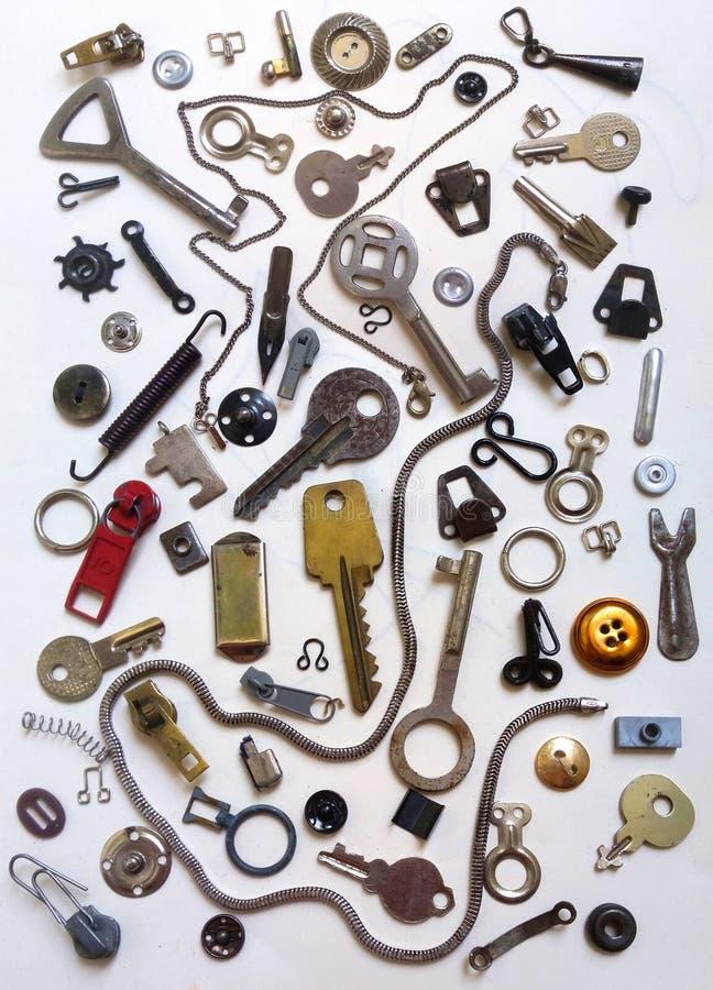 Sleutels, sloten, haken, kettingen en ander klein metaalmateriaal op de witte achtergrond stock foto's