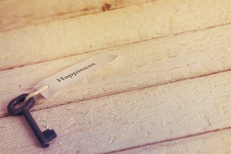 Sleutels tot Geluk - Keychain over witte Houten Achtergrond gestemd royalty-vrije stock afbeelding