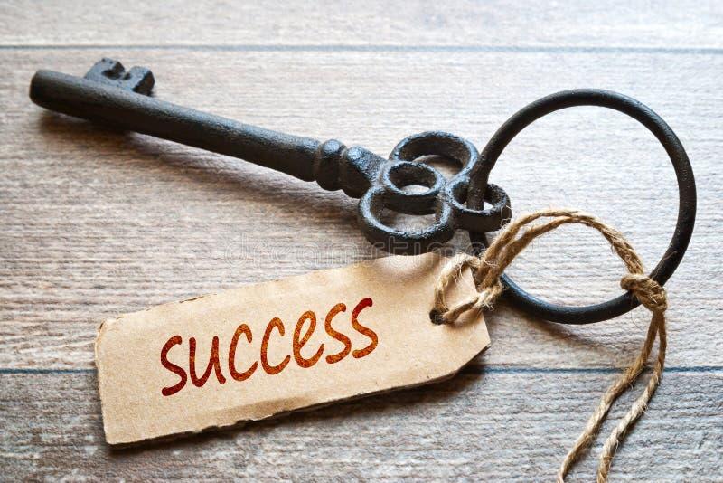 Sleutels tot Succes - Conceptenfoto Oude sleutel met document etiket op houten achtergrond - Succestekst stock fotografie