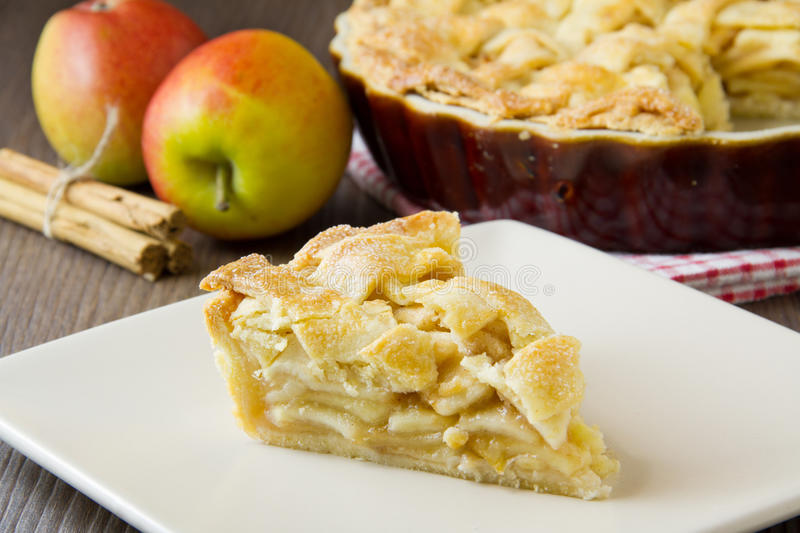 Slice of apple pie. Slice of freshly made apple pie with pastry lattice top, on flat plate with apples, cinnamon sticks and the rest of the pie out of focus stock photos