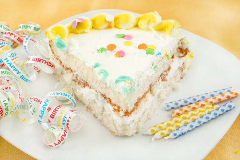 Slice of birthday cake. Slice of frosted festive birthday cake with candles and ribbon stock photography