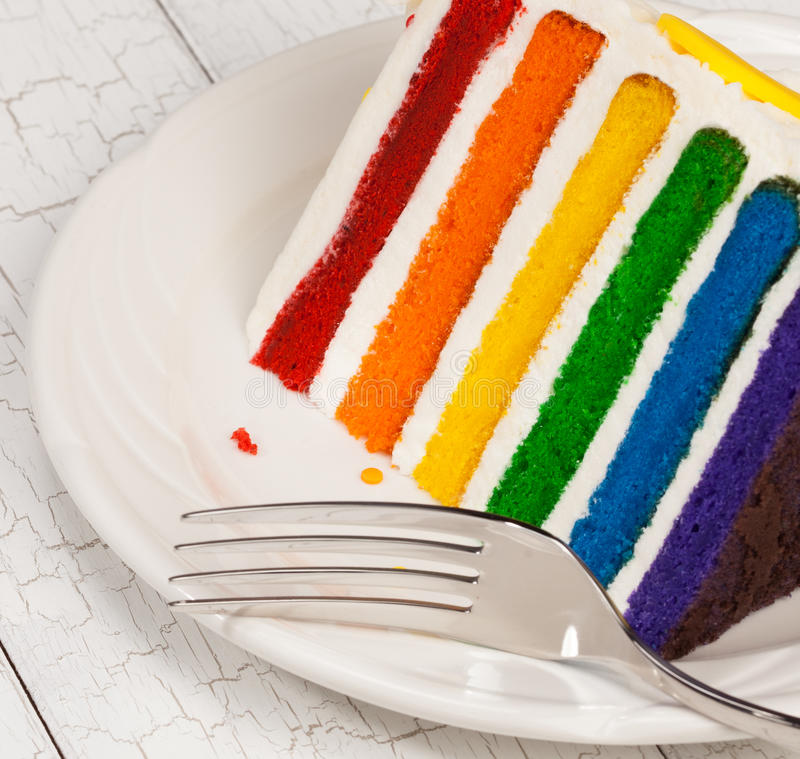 Slice of Birthday Cake. Slice of colourful rainbow layered birthday cake decorated with sprinkles and buttercream icing royalty free stock image