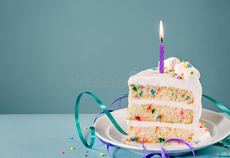 Slice of Birthday Cake. With a lit candle and ribbons over a blue background stock photography