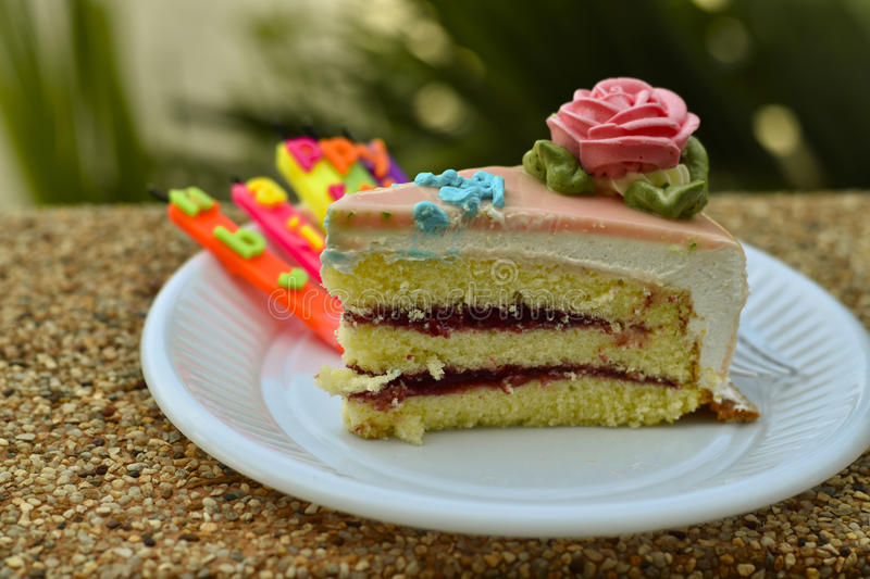 Slice of birthday cake with a lit candle in white plastic dish stock images