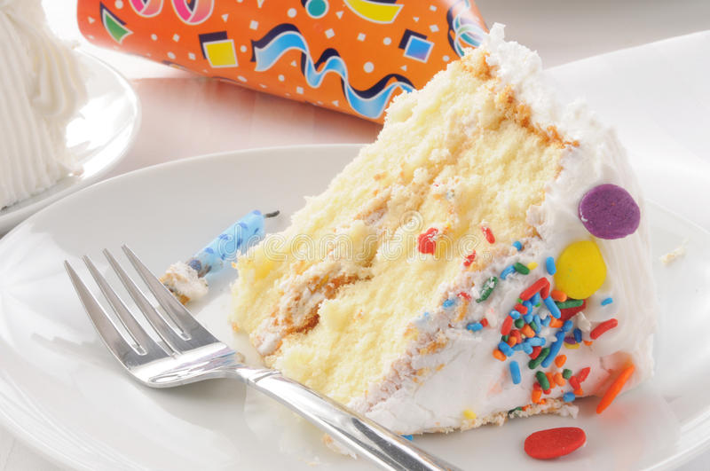 Slice of birthday cake and a party hat. Close up of a slice of birthday cake with a party hat royalty free stock images