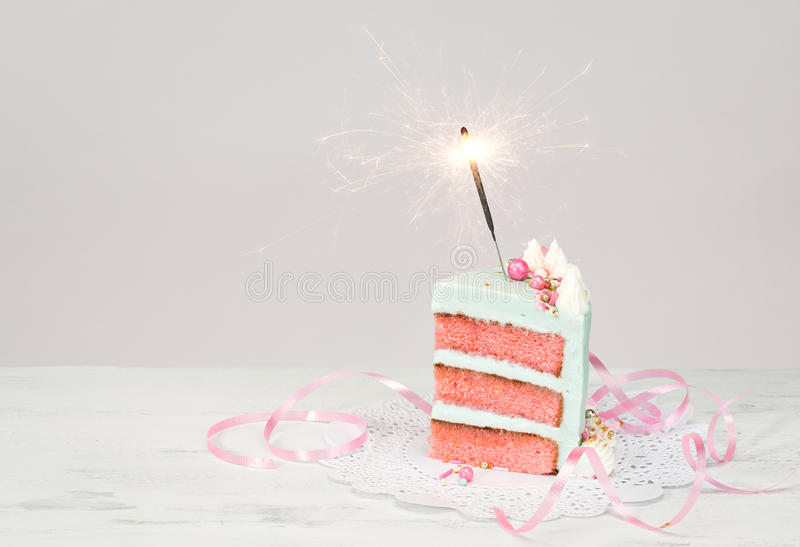 Slice of Birthday Cake with sparkler. Slice of birthday cake over white background with pink layers and sparkler royalty free stock photos