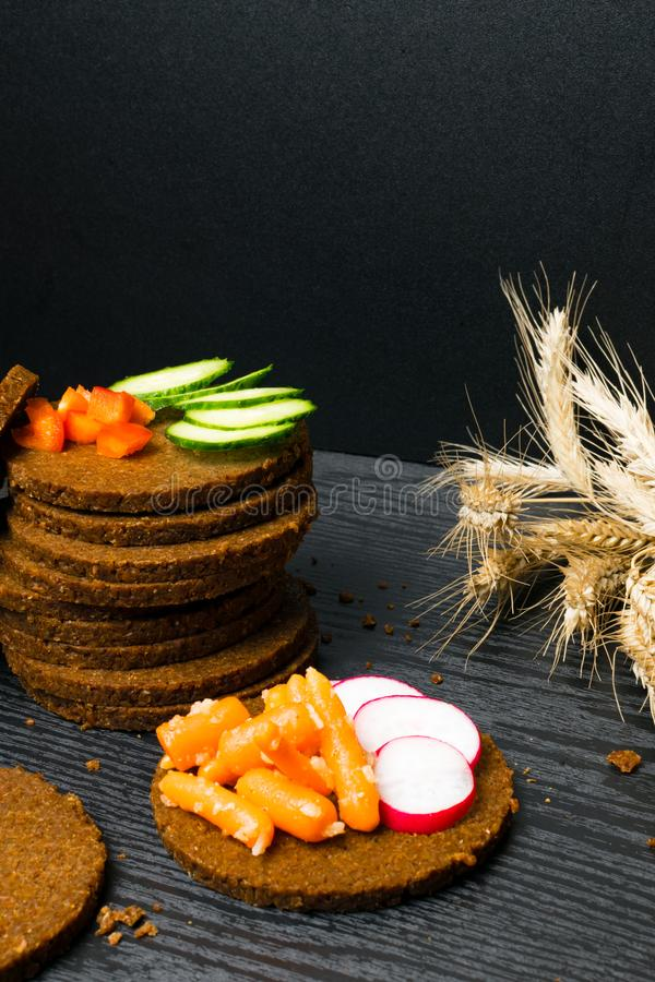 Slice of black bread with a cut in the shape of a heart with vegetables on dark wooden background. Health breakfast conception. Vi. Slice of black bread with a stock photography