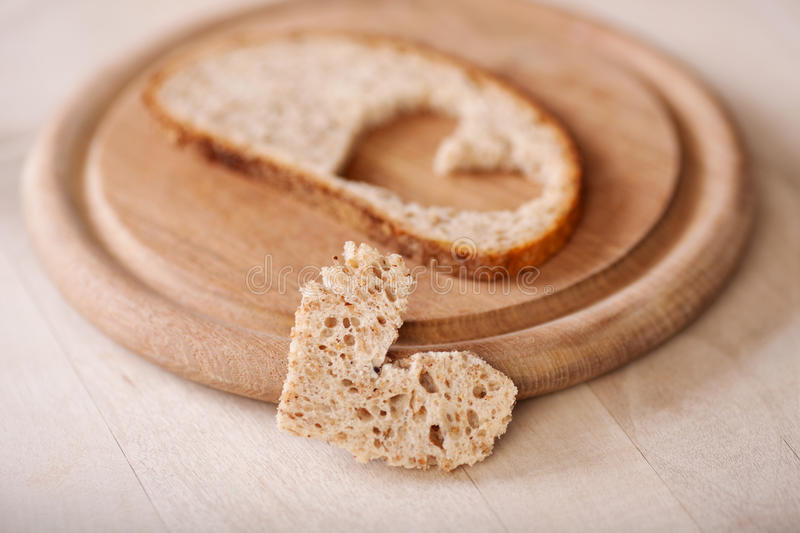 Slice of bread with a heart cut out. On wooden plate royalty free stock image