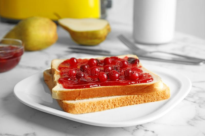 Slice of bread with jam on white marble. Table stock photos