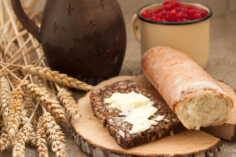 A slice of buttered bread on a wooden board, a crock of milk, a metal cup of red currants and mature ears. A summer composition with a slice of buttered bread on stock images