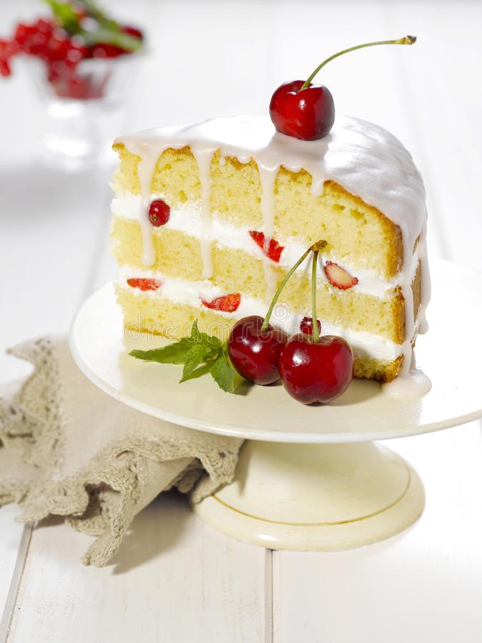 A slice of cake with fresh cherries royalty free stock images