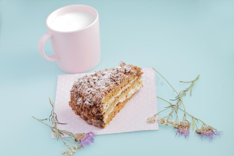 Slice of cake with icing on duck egg blue background with dried flowers and pink cup of milk stock images