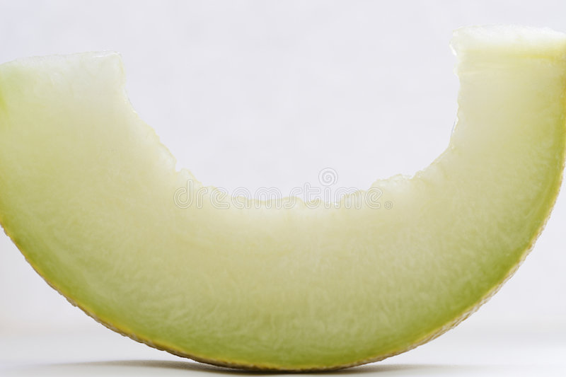 Slice of a cantaloupe. On a white background royalty free stock photos