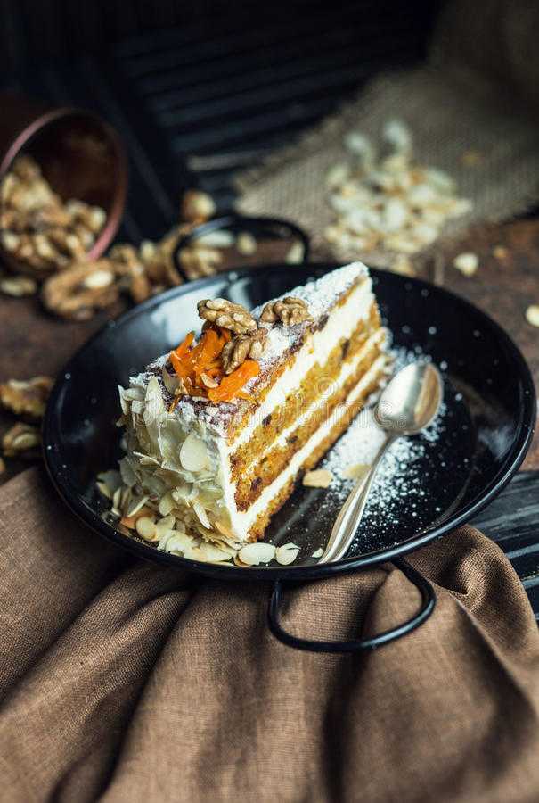 Slice of carrot cake with cream cheese and walnuts. The restaurant or cafe atmosphere. Vintage stock photos