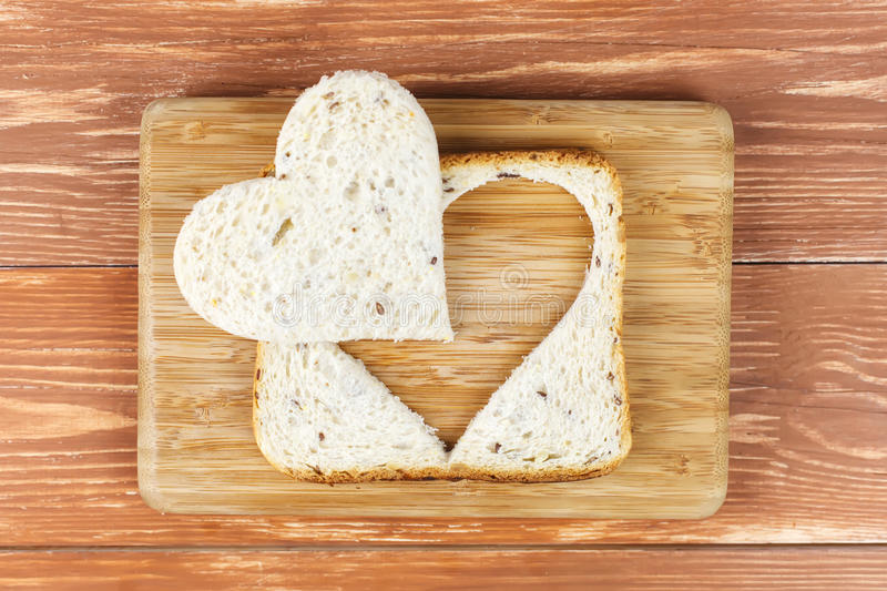 Slice of cereal toast bread with cut out heart. Slice of toast cereal bread with cut out heart shape stock photo