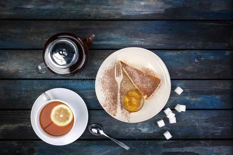 Slice of cheesecake with jam rafinated sugar and tea kettle with lemon on a colored wooden background. Top view.  royalty free stock photos
