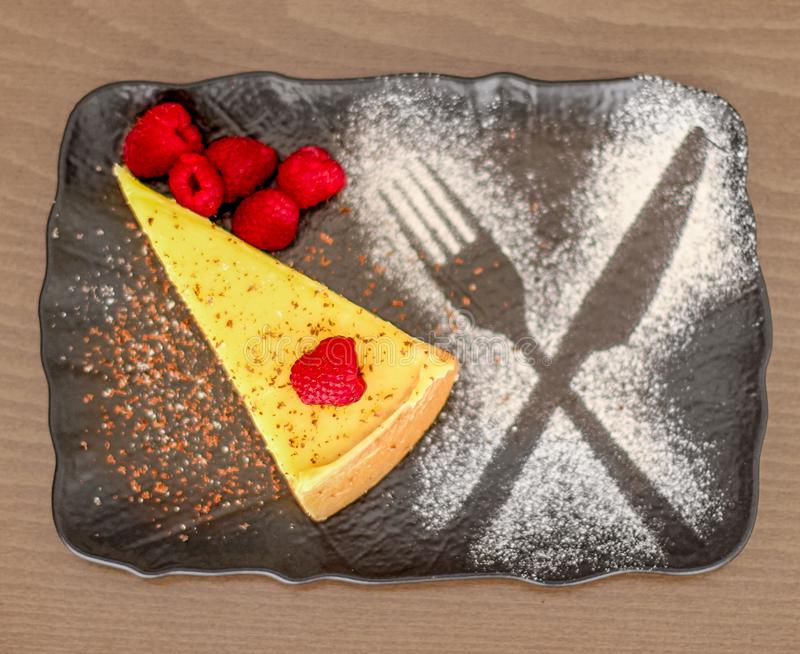 A slice of cheesecake with raspberry royalty free stock photo