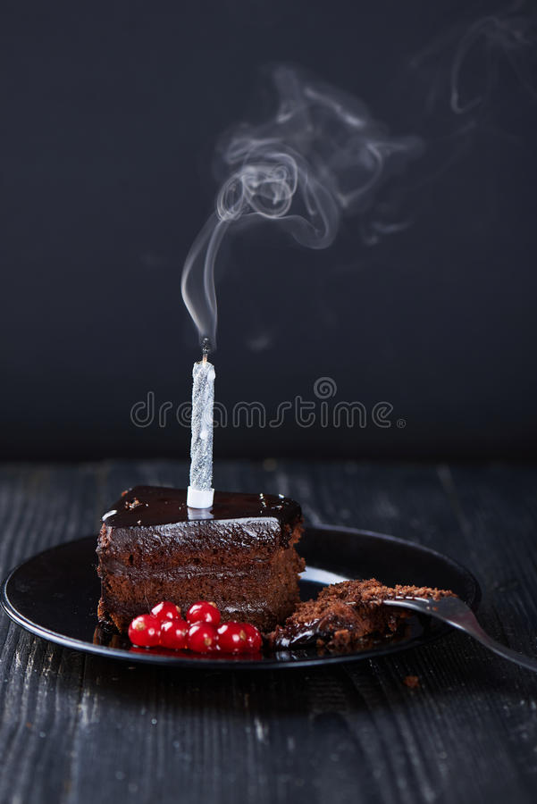 Slice of chocolate cake with a single lit candle. stock photos