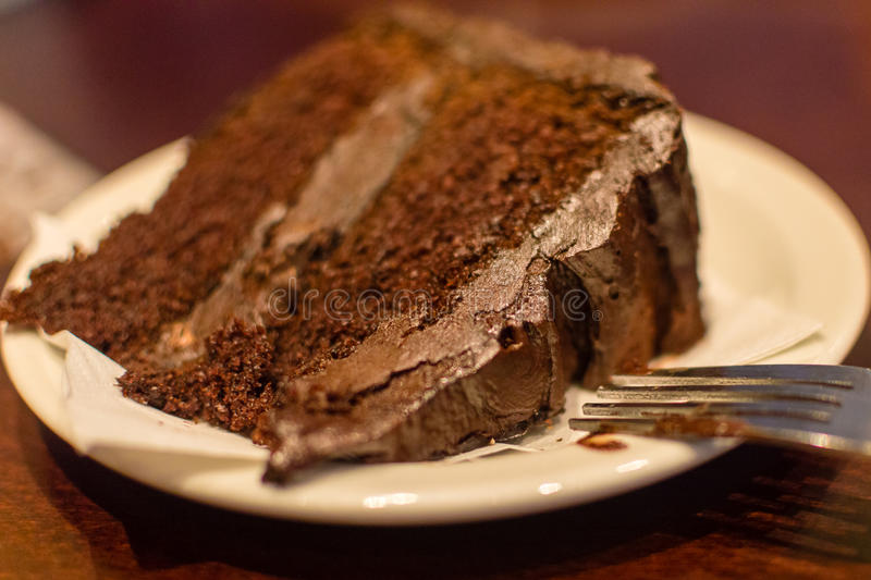 Slice of Chocolate Fudge Cake with fork on a plate A royalty free stock photo