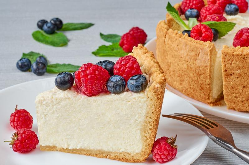 Slice of classic cheesecake with fresh berries on the white plate - healthy organic summer dessert. Cheese cake with blueberries stock image