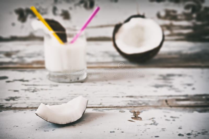 Slice of coconut over an old table. And coconut milk on background stock image