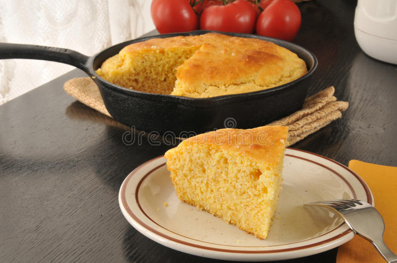 Slice of cornbread. A slice of fresh baked cornbread cooked in a cast iron skillet royalty free stock photography