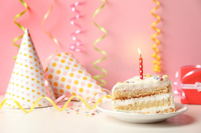 Slice of delicious birthday cake with candle. On table royalty free stock image