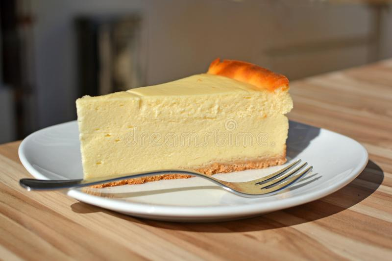 Slice of European Cheesecake on a dessert plate with spoon on table stock images