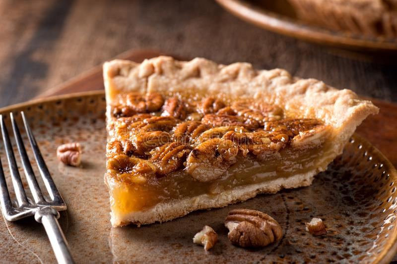 Pecan Pie. A slice of delicious home made pecan pie on a rustic table top royalty free stock photos