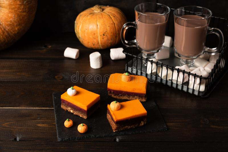A slice of delicious homemade pumpkin pie and glasses of hot chocolate royalty free stock photos