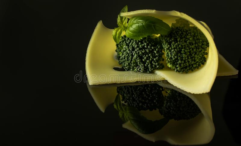 Slice Edamer cheese with broccoli and basil sprig royalty free stock photography