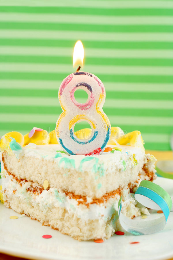 Slice of eighth birthday cake. Slice of eight birthday cake with lit candle, confetti, and ribbon (shallow depth of field stock image