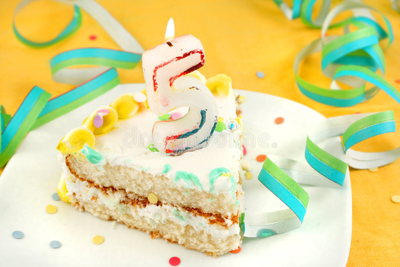Slice of fifth birthday cake. With lit candle, confetti, and ribbon royalty free stock photos